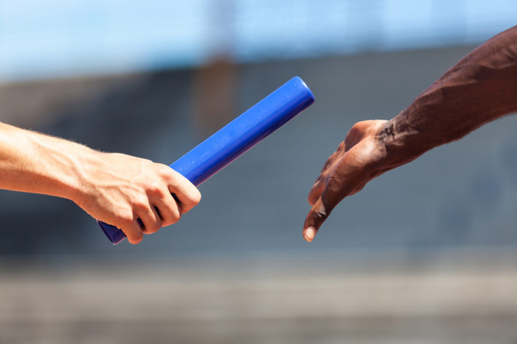 Image of a relay race with one athlete passing the baton to another