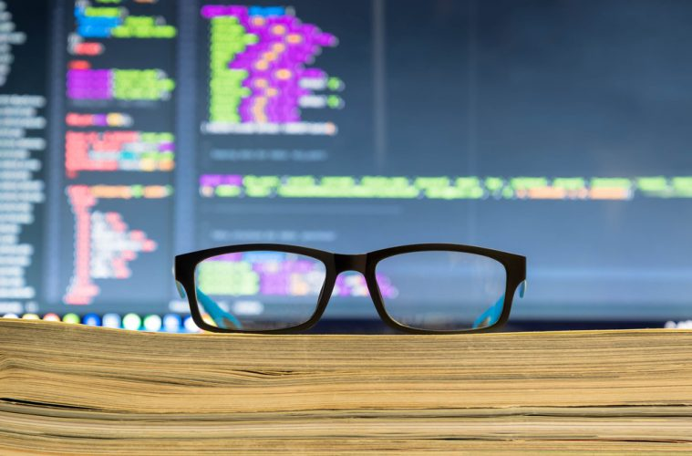 Image of pair of glasses in front of a computer screen,