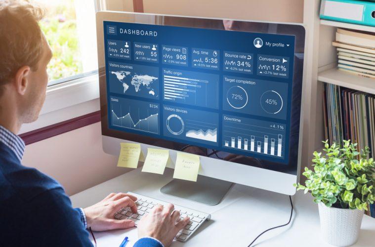 Image of man looking at metrics on computer screen